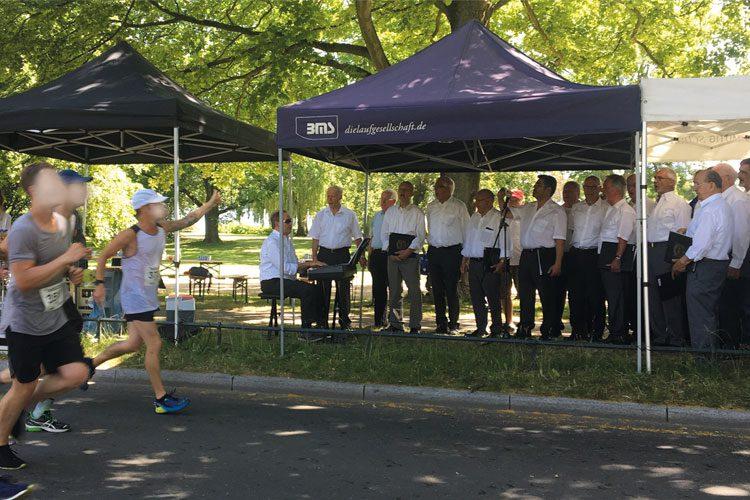 Männer singen am Rande der Marathon-Laufstrecke