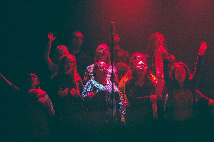 Chor auf der Bühne mit rotem Bühnenlicht