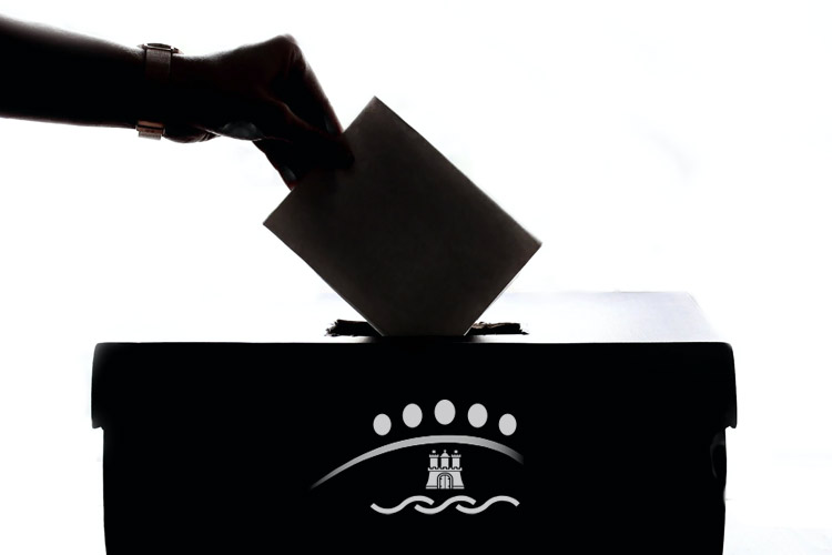 Hand wirft einen Brief in eine Wahlurne