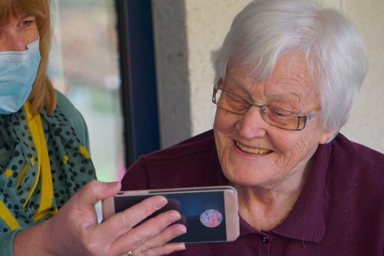Ältere Frau schaut auf ein Smartphone