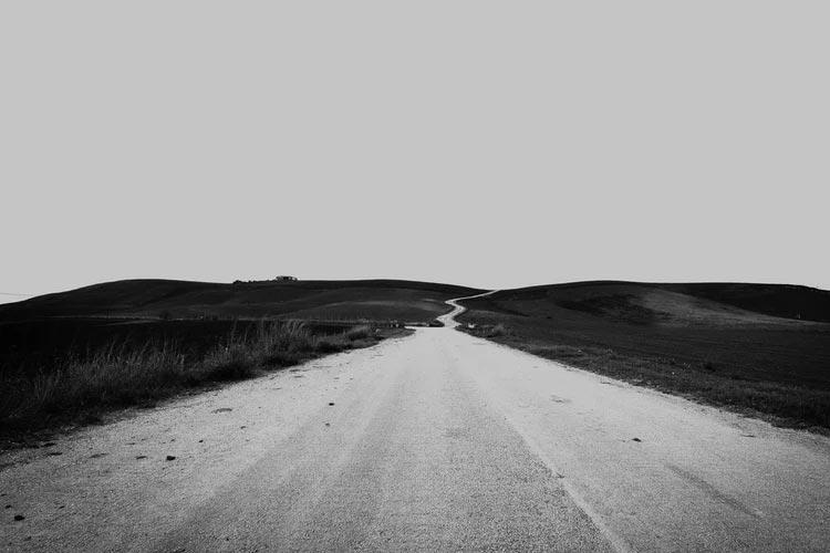 Einsame Straße führt geradeaus in den Horizont