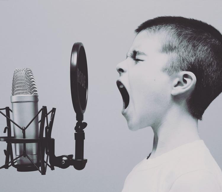 Junge singt mit weit offenem Mund in ein Studiomikrofon