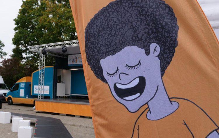 Fahne mit singendem Gesicht vor dem Singbus