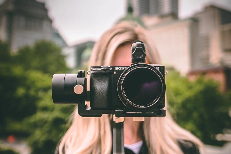 Blonde Frau steht hinter einer Videokamera